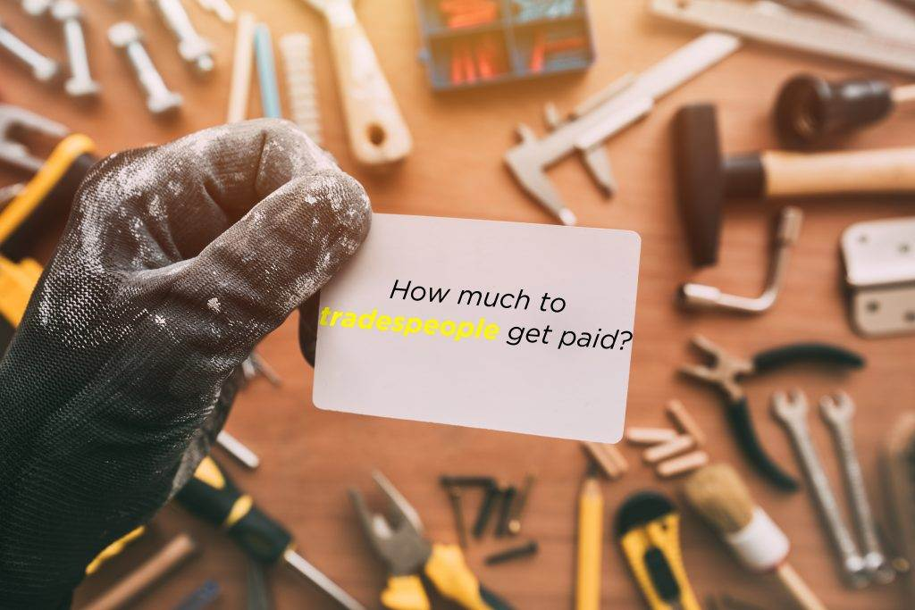 How Much do tradespeople get paid? A Man picks up a business card from a workbench